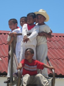Creole and Mestizo boys watch the dance on top of the slide.