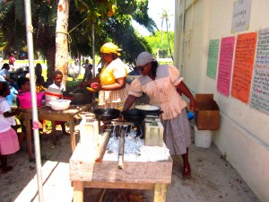 Parents cooking food at the Garifuna stand.